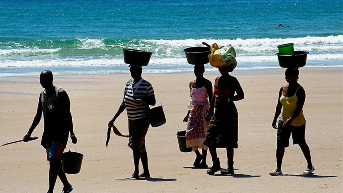 Mozambique - Vrouwen met emmers op hun hoofd op het strand