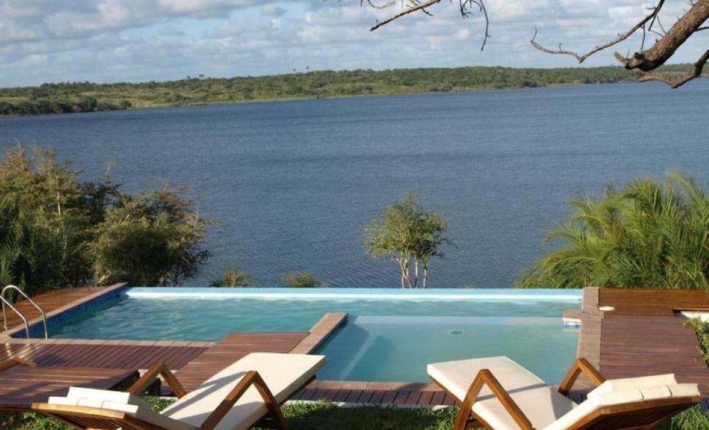 Naara Eco-Lodge - Zwembad met ligbedden en uitzicht over de baai