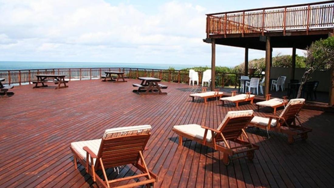 Sunset Beach Lodge - Terras met ligbedden en uitzicht op de baai