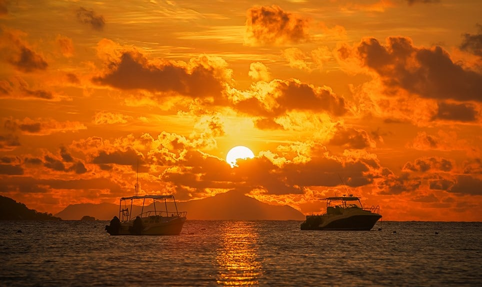 Rondreizen Seychellen - Wolken voor ondergaande zon over boten op oceaan