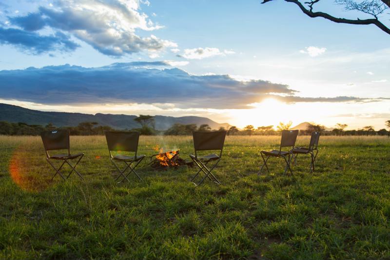 Huwelijksreizen Tanzania - Sundowner bij het kampvuur met uitzicht over de vlaktes van de Serengeti