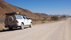 Kampeervoertuig naast onverharde weg Namibië